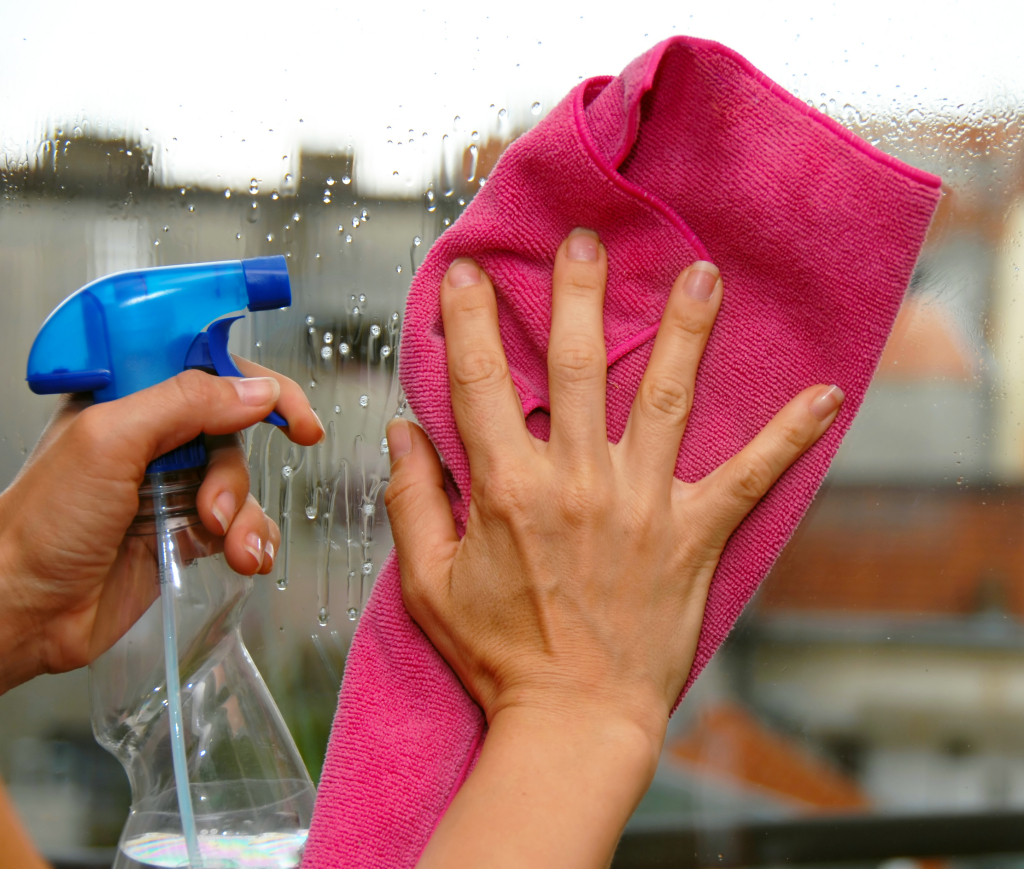 young woman hands on window cleaning a glass