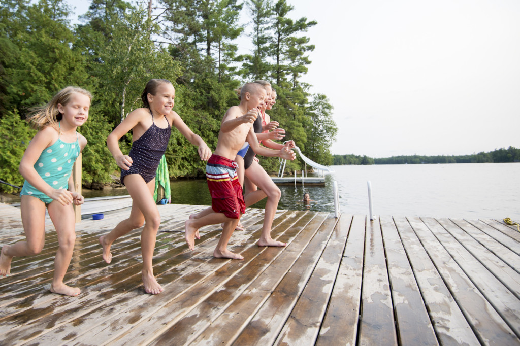 A group of children children running together on a floating dock in a lake on summer vacation.